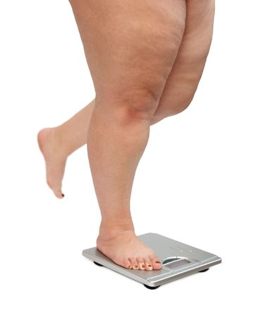 large build: women legs with overweight standing on scales