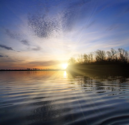 fishing scene: river landscape with sunset against ripple water Stock Photo