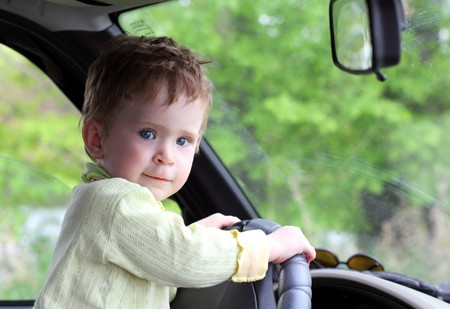 baby portrait holding steering wheel in car
