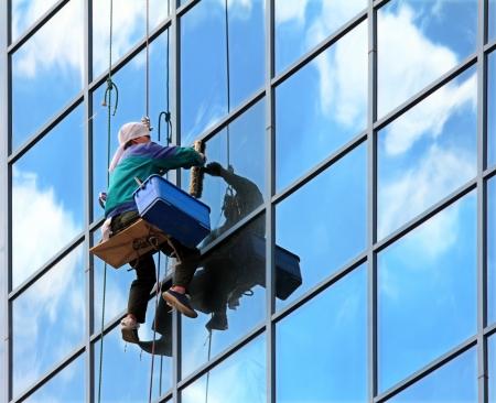 cleaners: Window cleaner opknoping op touw aan het werk op wolkenkrabber