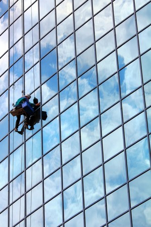 window cleaner hanging on rope at work on skyscraper photo