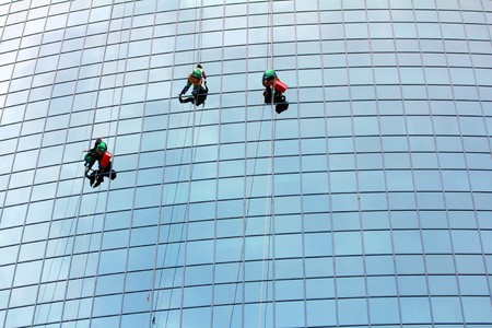 cleaning team: limpiacristales colgando de una cuerda en trabajan en rascacielos  Foto de archivo
