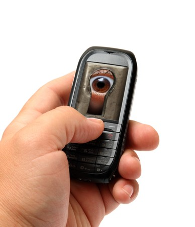 mobile phone in man hand with spy eye on screen photo