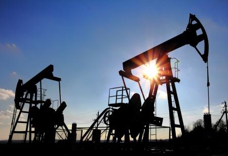 recursos naturales: dos bombas de petr�leo de trabajo silueta contra el sol