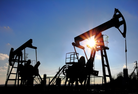 two working oil pumps silhouette against sun Stock Photo - 8107117