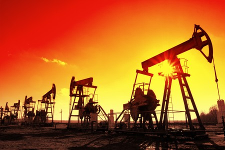 many working oil pumps silhouette in row against sun photo