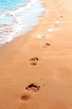 voet afdrukken op zand strand langs de rand van de zee Stockfoto