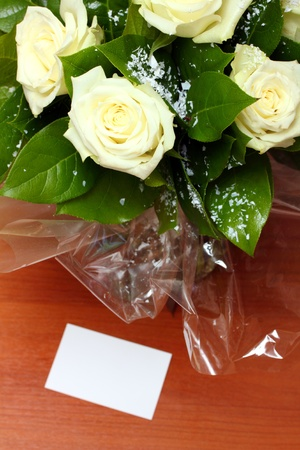 greetings - bouquet of white roses and note on table photo