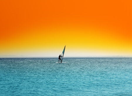 Windsurfen - Surfer auf blauem Meer unter orange Himmel