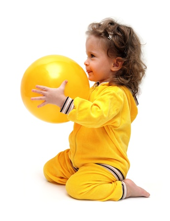 barefoot girls: cute little girl in yellow playing with ball