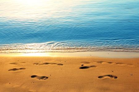 voetafdrukken op zand strand langs zee bij zonsopgang