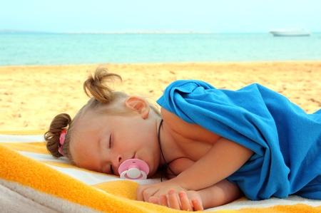kleines Mädchen am Strand in der Nähe von Meer schlafen