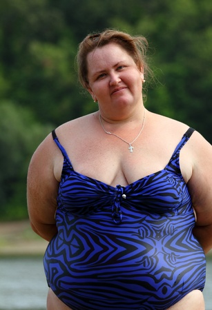 donne obese: portarit di donna paffuta in piedi vicino al fiume