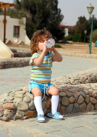 little girl drinking from bottle - outdoor photo photo