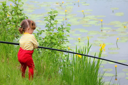 fishing littlle girl with rod on pond coast photo