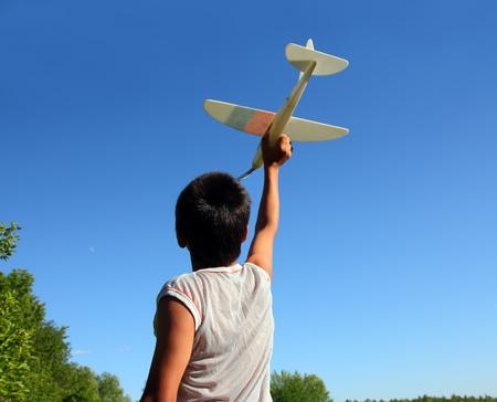 happy boy running airplane model under blue sky