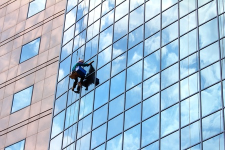 clean window: window cleaner hanging on rope at work on skyscraper Stock Photo
