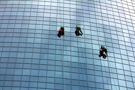cleaning an office: window cleaners hanging on rope at work on skyscraper