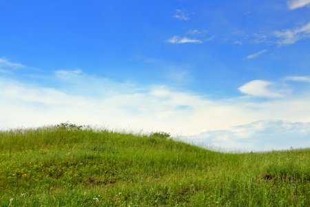 over the hill: landscape with green grass hill under blue sky