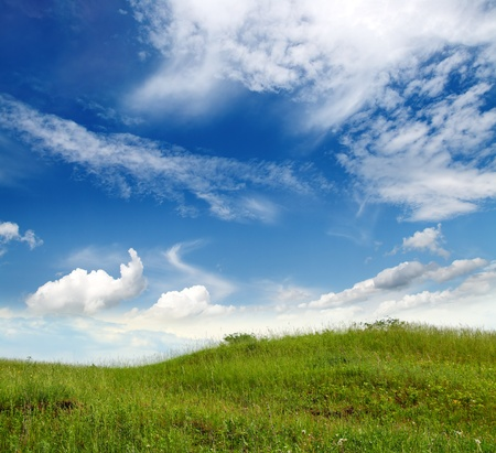 landscape with green grass hill under blue sky photo