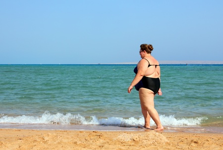 overweight woman walking on sea beach Stock Photo
