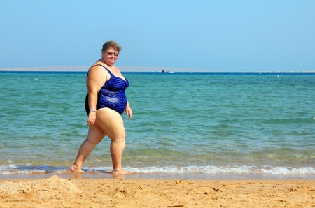 adult only: overweight woman walking on sea beach Stock Photo