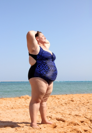 Übergewicht Frau, die am Strand mit hands up