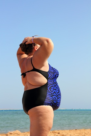 1 woman only: overweight woman standing on beach with hands up