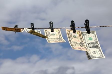 paper dollars are drying on rope under blue sky photo