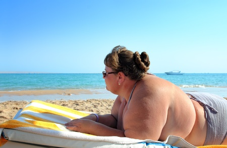 upset stomach: vacation - overweight woman lying on beach