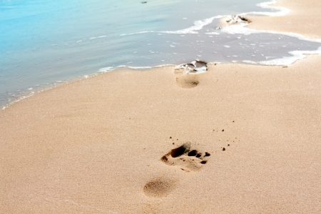footprints on sand beach along the edge of sea Stock Photo
