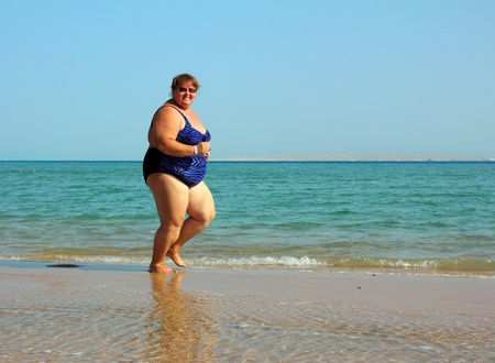 fitness - overweight woman running on sea coastline Stock Photo