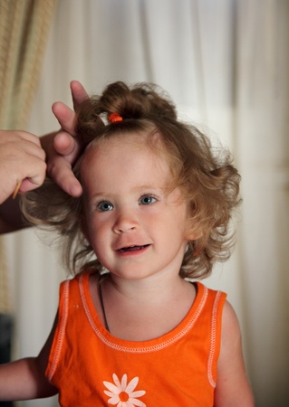 little girl combing hair by mother photo
