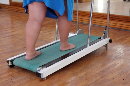 persevere: fitness - overweight woman legs on trainer treadmill