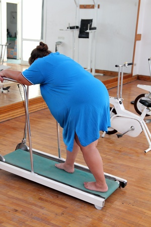 fitness - overweight woman running on trainer treadmill photo