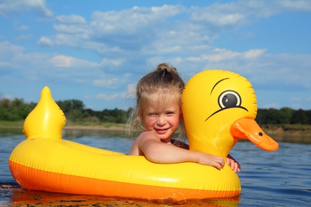 little girl bathes in summer river in inflatable duck photo