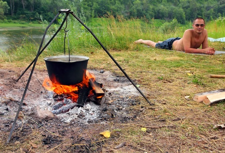 camping - kettle over campfire and lying tourist photo