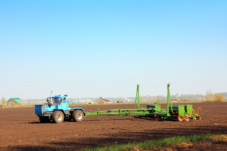 seed drill: agriculture tractor with drill on field Editorial