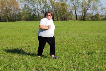 sport - overweight woman running on green meadow Stockfoto