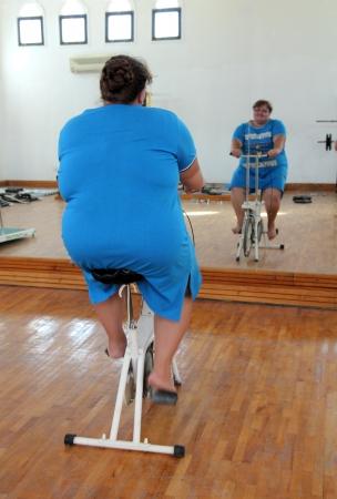 simulator: overweight woman exercising on bike simulator