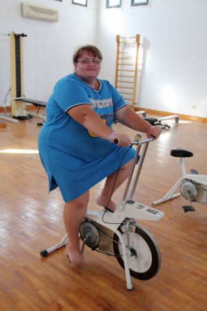 overweight woman exercising on bike simulator Reklamní fotografie - 14008983