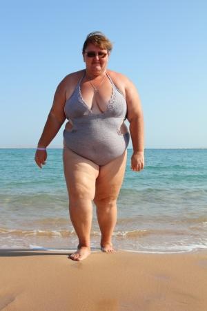overweight woman walking on beach near sea Stockfoto