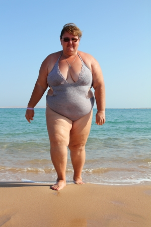 belly fat: overweight woman walking on beach near sea Stock Photo