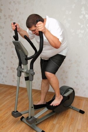 overweight man exercising on trainer ellipsoid  Stock Photo