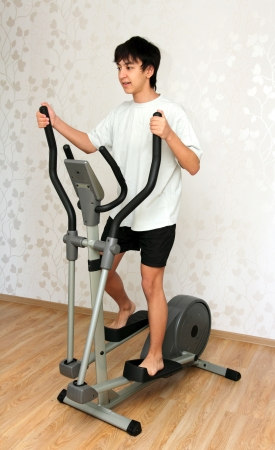 boy exercising on trainer ellipsoid photo