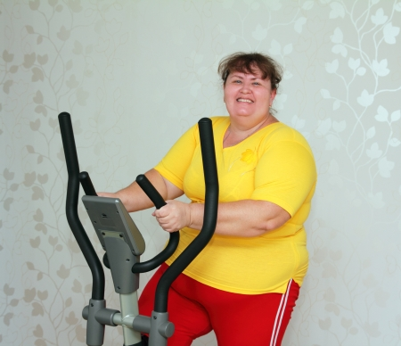 overweight woman exercising on trainer ellipsoid photo