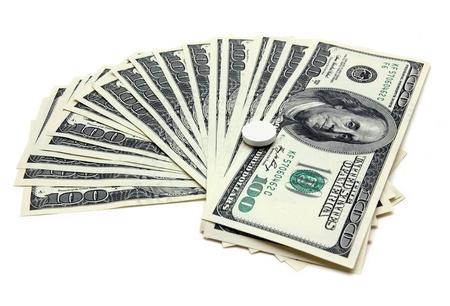 hospital expenses: expensive medicine - pill on the hundred-dollar bills
