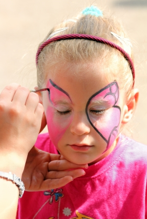 face paint: artist paints butterfly on face of cute little girl Stock Photo