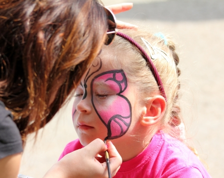 artist paints butterfly on face of cute little girl 스톡 콘텐츠