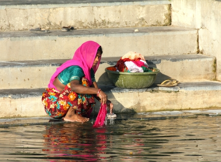 UDAIPUR, INDIA - NOVEMBER 23, 2012: Indian woman washing clothes in the lake in Udaipur, India, 23 nov 2012